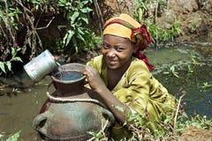 Αιθιοπικό προσκομίζοντας νερό κοριτσιών στο φυσικό φρεάτιο νερού Στοκ εικόνα με δικαίωμα ελεύθερης χρήσης