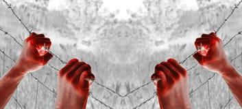 Αιματηρό βασανισμένο χέρι που πιάνει απελπισμένα τα οδοντωτά καλώδια Στοκ φωτογραφία με δικαίωμα ελεύθερης χρήσης
