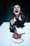 Αιματηρό θέμα αποκριών: τρελλό κορίτσι με ένα μαχαίρι, ένα δίκρανο και ένα κρέας Στοκ εικόνα με δικαίωμα ελεύθερης χρήσης