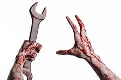 Αιματηρό χέρι που κρατά ένα μεγάλο γαλλικό κλειδί, αιματηρό γαλλικό κλειδί, μεγάλο βασικό, αιματηρό θέμα, θέμα αποκριών, τρελλό μ Στοκ Φωτογραφία