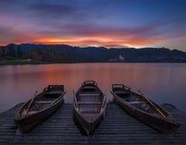 Αιμορραγημένος, Σλοβενία - οι παραδοσιακές βάρκες στη λίμνη αιμορράγησαν με το όμορφο δραματικό ηλιοβασίλεμα Στοκ φωτογραφία με δικαίωμα ελεύθερης χρήσης