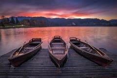 Αιμορραγημένος, Σλοβενία - οι παραδοσιακές βάρκες στη λίμνη αιμορράγησαν με το όμορφο δραματικό ηλιοβασίλεμα Στοκ Φωτογραφίες