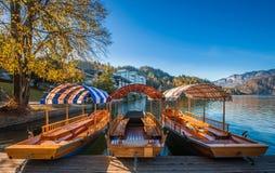 Αιμορραγημένος, Σλοβενία - παραδοσιακές κόκκινες, πορτοκαλιές και μπλε βάρκες Pletna στην ηλιοφάνεια φθινοπώρου Στοκ Φωτογραφίες