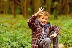 Αισθάνομαι εντάξει Το μικρό παιδί παρουσιάζει εντάξει σημάδι αγόρι ευτυχές λίγα Το μικρό αγόρι απολαμβάνει την ημέρα στα ξύλα Ακρ στοκ φωτογραφίες
