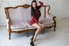 Αισθησιακή γυναίκα με την τέλεια τοποθέτηση σωμάτων σε ένα κόκκινο κοντό φόρεμα Στοκ φωτογραφία με δικαίωμα ελεύθερης χρήσης