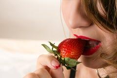 Αισθησιακή γυναίκα που τρώει τη φράουλα Στοκ Εικόνες