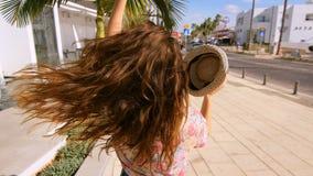 Αισθησιακή γυναίκα στο καπέλο που περπατά στην τροπική πόλη Απολαύστε τις καλοκαιρινές διακοπές φιλμ μικρού μήκους