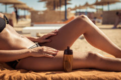 Αισθησιακή λεπτή γυναίκα που εφαρμόζει το suntan πετρέλαιο Στοκ Εικόνες