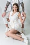 Αισθησιακή κομψή συνεδρίαση ζευγών που αγκαλιάζεται, άνδρας πίσω από τη γυναίκα στο άσπρο φόρεμα που κρατά στενό της Στοκ φωτογραφία με δικαίωμα ελεύθερης χρήσης