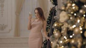 Αισθησιακή νέα γυναίκα στο ρόδινο φόρεμα που εξετάζει wineglass και το χαμόγελο απόθεμα βίντεο