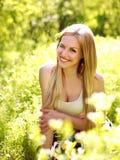 Αισθησιακή νέα γυναίκα, χαμόγελα γλυκά στον ανθισμένο κήπο Στοκ Εικόνες