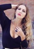 Αισθησιακή νέα μοντέρνη κυρία γοητείας που φορά τα καθιερώνοντα τη μόδα μαύρα drress Στοκ Φωτογραφία