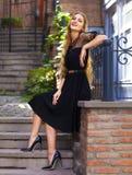 Αισθησιακή νέα μοντέρνη κυρία γοητείας που φορά τα καθιερώνοντα τη μόδα μαύρα drress Στοκ Εικόνες