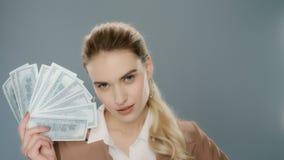 Αισθησιακός ανεμιστήρας χρημάτων εκμετάλλευσης γυναικών Νέα επιχειρησιακή γυναίκα που παρουσιάζει ανεμιστήρα μετρητών χρημάτων απόθεμα βίντεο
