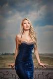 Αισθησιακός ξανθός με την κομψή μπλε τοποθέτηση φορεμάτων στο λ στοκ φωτογραφία
