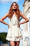 Αισθησιακό καυκάσιο νέο πρότυπο γυναικών με το βράδυ makeup στην άσπρη τοποθέτηση θερινών φορεμάτων στο υπόβαθρο οδών Στοκ Φωτογραφία
