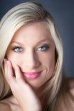 Αισθησιακό ξανθό θηλυκό χαμόγελο που κρατά το πρόσωπό της Στοκ Εικόνες