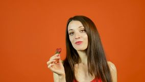 Αισθησιακό σαγηνευτικό ενήλικο κορίτσι που τρώει την κόκκινη ώριμη φράουλα στο πορτοκαλί υπόβαθρο στο στούντιο απόθεμα βίντεο