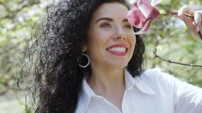 Αισθησιακό brunette με το ρόδινο magnolia απόθεμα βίντεο