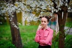 αισθησιασμός Ευτυχής όμορφη νέα χαλάρωση γυναικών στο πάρκο ανθών στοκ εικόνες