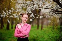 αισθησιασμός Ευτυχής όμορφη νέα χαλάρωση γυναικών στο πάρκο ανθών στοκ εικόνα