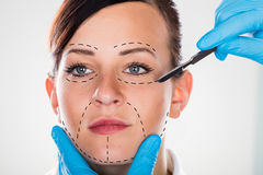 Αισθητική χειρουργική με το χειρουργικό νυστέρι στη νέα γυναίκα στοκ φωτογραφίες
