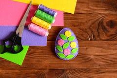 Αισθητό ντεκόρ αυγών Πάσχας, ψαλίδι, ομάδα νημάτων, βελόνα, χρωματισμένα αισθητά φύλλα στο ξύλινο υπόβαθρο με το διάστημα αντιγρά Στοκ εικόνα με δικαίωμα ελεύθερης χρήσης
