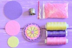 Αισθητό λουλούδι, χρωματισμένοι αισθητοί κύκλοι, στροφία νημάτων, βελόνα, δακτυλήθρα, ρόδινες χάντρες σε έναν ξύλινο πίνακα Ράψιμ Στοκ φωτογραφία με δικαίωμα ελεύθερης χρήσης