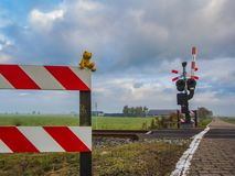 Αισιόδοξος ένας teddy αντέχει κάθεται σε ένα πέρασμα σιδηροδρόμων και εξετάζει την απόσταση με τη μεγάλη επιθυμία Ταξίδι, μοναξιά στοκ φωτογραφία