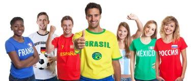 Αισιόδοξος βραζιλιάνος υποστηρικτής ποδοσφαίρου με τους ανεμιστήρες από άλλη αρίθμηση στοκ φωτογραφία με δικαίωμα ελεύθερης χρήσης