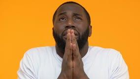 Αισιόδοξος νεαρός άνδρας που διασχίζει τα δάχτυλα για την καλή τύχη, προσευμένος τα ενώνοντας χέρια, τύχη φιλμ μικρού μήκους