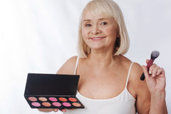 Αισιόδοξη ηλικίας γυναίκα που χρησιμοποιεί μια παλέτα ρουζ Στοκ Φωτογραφίες