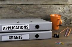 Αιτήσεις και επιχορηγήσεις - δύο φάκελλοι στο ξύλινο γραφείο γραφείων Στοκ Φωτογραφίες