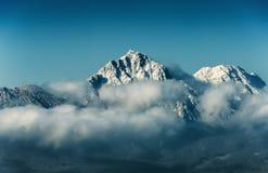 Αιχμή βουνών με το χιόνι στο σύννεφο στο υπόβαθρο μπλε ουρανού Στοκ φωτογραφία με δικαίωμα ελεύθερης χρήσης