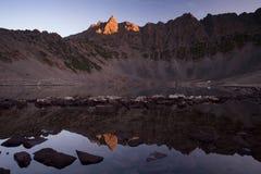 Αιχμή βουνών σε ένα κόκκινο φως και η αντανάκλασή του στο νερό Στοκ Φωτογραφία