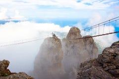 Αιχμή βουνών στα σύννεφα με μια γέφυρα αναστολής κλιμακοστάσιο στον ουρανό στοκ φωτογραφίες με δικαίωμα ελεύθερης χρήσης