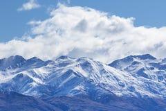 Αιχμή του χιονιού βουνών με το άσπρους σύννεφο και το μπλε ουρανό Στοκ εικόνα με δικαίωμα ελεύθερης χρήσης