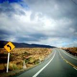 Αιχμηρή αριστερή κάμψη στο δρόμο για την οδήγηση στο δρόμο ερήμων, Νέα Ζηλανδία, Στοκ Εικόνα