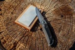 Αιχμηροί μαχαίρι και ακονόλιθος σε ένα ξύλινο υπόβαθρο στοκ εικόνες