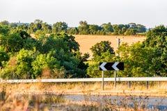 Αιχμηρό κατευθυντικό σημάδι στροφής στο βρετανικό δρόμο πέρα από το αγροτικό lanscape επαρχίας στοκ εικόνες με δικαίωμα ελεύθερης χρήσης