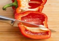 Αιχμηρό μαχαίρι που κόβει το φρέσκο κόκκινο πιπέρι κουδουνιών στα τέταρτα, κινηματογράφηση σε πρώτο πλάνο Στοκ φωτογραφία με δικαίωμα ελεύθερης χρήσης