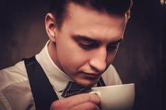 Αιχμηρό ντυμένο άτομο που φορά το γιλέκο με ένα φλιτζάνι του καφέ Στοκ εικόνα με δικαίωμα ελεύθερης χρήσης