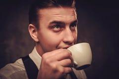Αιχμηρό ντυμένο άτομο που φορά το γιλέκο με ένα φλιτζάνι του καφέ Στοκ Εικόνες
