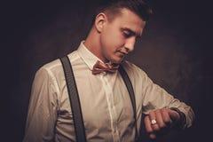 Αιχμηρό ντυμένο άτομο που φορά το δεσμό τόξων που εξετάζει το wristwatch στοκ φωτογραφία με δικαίωμα ελεύθερης χρήσης