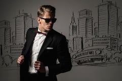 Αιχμηρό ντυμένο άτομο στο μαύρο κοστούμι ενάντια στην πόλη Στοκ Εικόνα