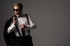 Αιχμηρό ντυμένο άτομο στο μαύρο κοστούμι με το μπουκάλι του κρασιού Στοκ Φωτογραφία
