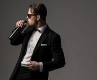 Αιχμηρό ντυμένο άτομο στο μαύρο κοστούμι με το μπουκάλι του κρασιού Στοκ Εικόνες
