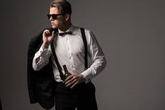 Αιχμηρό ντυμένο άτομο στο μαύρο κοστούμι με το μπουκάλι του κρασιού Στοκ εικόνα με δικαίωμα ελεύθερης χρήσης