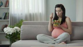 Αιώνια πεινασμένο έγκυο κορίτσι που τρώει τη σαλάτα, που διαποτίζει το σώμα με τις βιταμίνες απόθεμα βίντεο