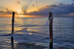 Αιώρα πέρα από τη θάλασσα στο ηλιοβασίλεμα Στοκ Φωτογραφία